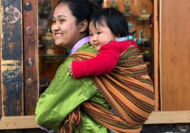 Bhutanese mother carries her child on her back